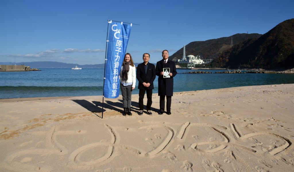 CNIC members stand in front of Monju (from right to left Baku Nishio (holding a photo of CNIC founder, Jinzaburo Takagi), Hideyuki Ban, Caitlin Stronell) In the sand is written 'Sayonara.' At the national rally to decommission Monju on 3 December, 2016 (Photo by Ryohei Kataoka, CNIC)
